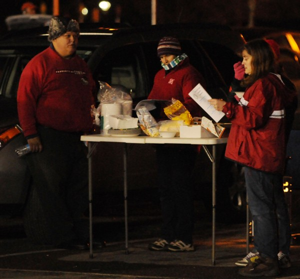 Cony Rams fans eat food off a plastic table in a parking lot at the University of Maine before the Cony-Kennebunk Class B state championship football game on Friday in Orono.