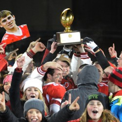 Cony High School football players carry the Class B state football championship trophy into the crowd of fans waiting at the end of the field at Alfond Stadium on Friday  after defeating Kennebunk 30-23.
