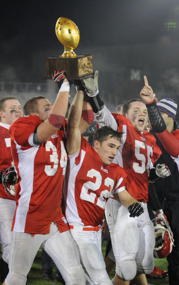 Cony's Shukri Hallak,  John Bennett and Nicholas Benner carry the Class B state football trophy after defeating Kennebunk 30-23 at Orono during the Class B state championship game on Friday.