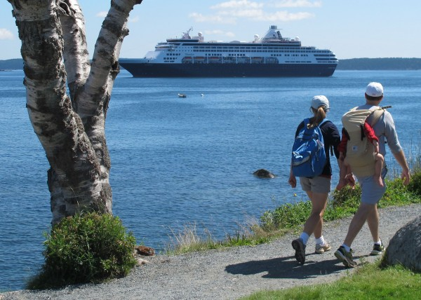 A couple carrying a small child stroll along Bar Harbor's Shore Path on Sunday, Aug. 4, 2013 while the cruise ship Maasdam sits anchored offshore in Frenchman Bay.