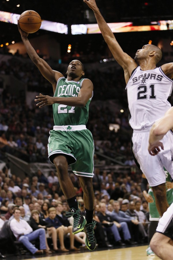 Boston Celtics guard Jordan Crawford (27) drives to the basket under pressure from San Antonio Spurs forward Tim Duncan (21) during the first half Wednesday night in San Antonio.