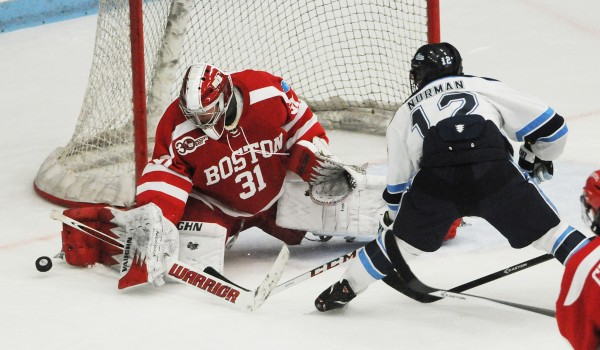 Boston University goalie Sean Maguire watches the puck slide by as UMaine's BIll Norman misses the chance to score during first period action on Friday at Orono.