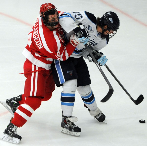 UMaine's Ben Hutton and Boston University's Robbie Baillargeon battle for control of the puck during first period action on Friday at Orono.