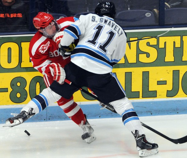 UMaine's Steven Swavely checks Boston University's Matt Grzelcyk during first period action on Friday at Orono.