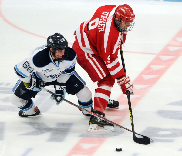 UMaine's Brian Morgan battles for the puck with Boston University's Sam Kurker during first period action on Friday at Orono.