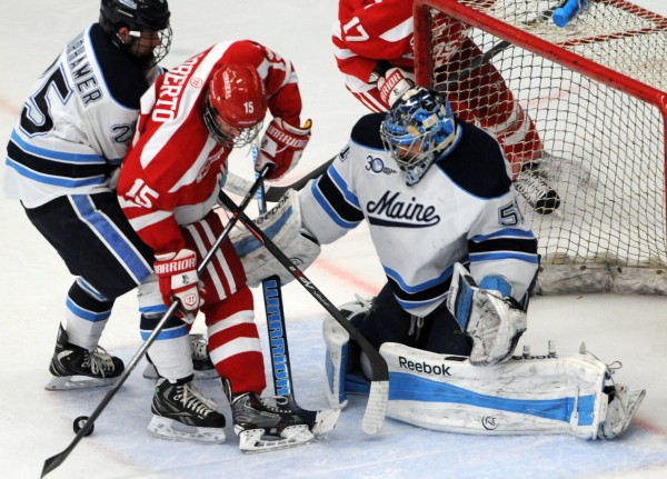 UMaine's goalie Martin Ouellette tries to keep the puck in sight as Boston University's Nick Roberto attempts to score, helping out on the play is UMaine's Eric Schurhamer during first period action on Friday at Orono.