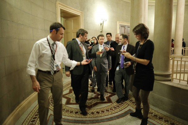 U.S. Sen. Rand Paul (C) is flanked by reporters as he arrives for a Republican Senate caucus meeting at the U.S. Capitol in Washington, October 16, 2013.