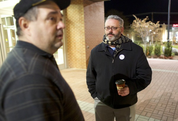 City council candidate Gibran Graham, right, talks with Joe Cutrufello, left, while Graham greeted voters as they enter to cast their ballots at the Cross Insurance Center Tuesday evening in Bangor.