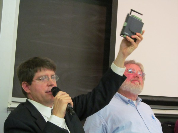 David Clay of Mechanical Services Inc. holds up a small device that monitors and manages a building's energy systems during a forum Thursday on carbon emissions in South Portland. The same device was about the size of a refrigerator in the 1970s, Clay said.