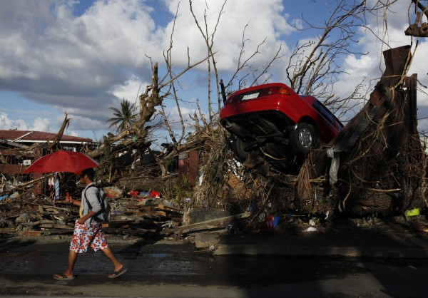 A resident walks past a car which landed amid fallen trees in Tacloban, after super Typhoon Haiyan battered the city in central Philippines, November 18, 2013.