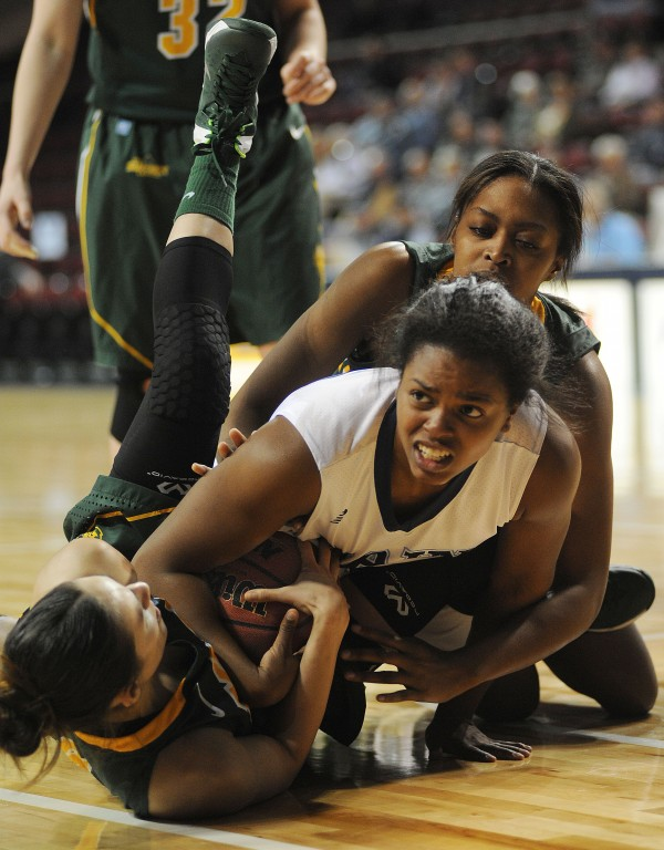 UMaine's Ashleigh Roberts gets the foul after she was pushed from behind by North Dakota State's Catavia Jones while wrestling for a loose ball with North Dakota State's Brooke LeMar during first half action on Thursday at Bangor's Cross Insurance Center.