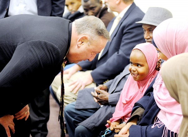 Mouna Ismail and her 4-year-old daughter, Ibtissan Abdi, hidden, has their picture taken with Gov. Paul LePage at the B Street Community Center in Lewiston on Monday. LePage met with local immigrants to hear about the challenges they face in trying to find employment.