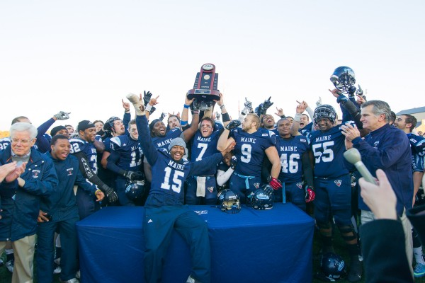 University of Maine football players hold their CAA championship trophy after their 41-0 win against Rhode Island last Saturday in Orono.
