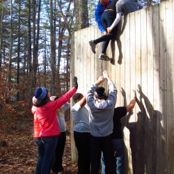 Trekkers in the Leadership Training Program using teamwork to ascend the stockade fence.