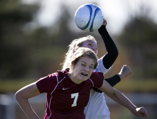 Bangor's Emily Smith and Windham's Cassie Symonds attempt to head a throw-in from the sidelines in the second half of the Class A girls soccer state championship, Saturday, Nov. 9, 2013, in Bath, Maine.