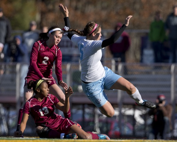 Windham's Ciera Berthiaume (right) gets tripped up by Bangor defenders Emily Brookings (2) and Tiffany Gray in the first half of the Class A girls soccer state championship, Saturday, Nov. 9, 2013, in Bath, Maine.