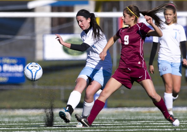 Windham's Ariana Davidson (left) gets off a pass against Bangor's Anna-Marie Dagher  in the first half of the Class A girls soccer state championship, Saturday, Nov. 9, 2013, in Bath, Maine.