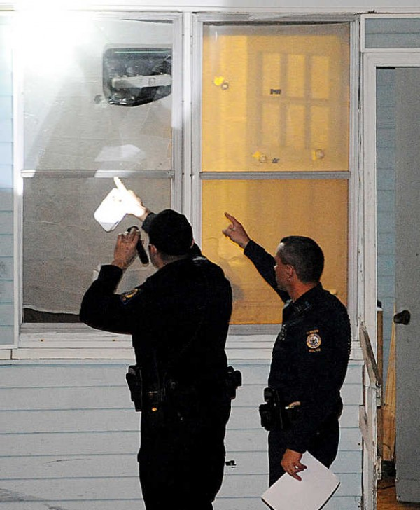 Auburn police point to what appears to be a bullet hole as they investigate a report of shots fired at 14 Newbury St. in Auburn on Wednesday evening.