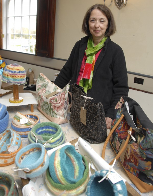 Weekly Photo by Brian Swartz  During the Hampden Garden Club craft fair held Oct. 26 at Harmony Hall on Kennebec Road, Cristina Anderson of Bangor displays the crocheted and felted baskets that she designs and creates. Now a Bangor School Department teacher, she started crocheting when she was 7.