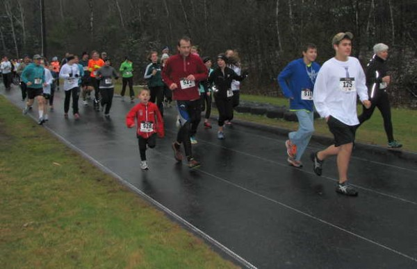 Participants in Saturday afternoon's Running for Randy 5k cross-country race sprint down the Spruce Mountain High School track before heading around the field and into the woods.