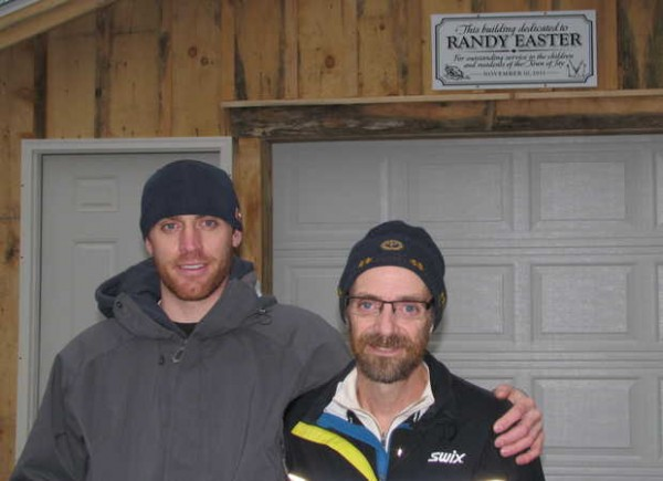 Following a Jay ceremony on Saturday on Lavoie Street Extension, runner, race-walker and skier Justin Easter, left, stands with his father, Randy Easter, in front of the town's new trail-grooming equipment building dedicated to Randy Easter.