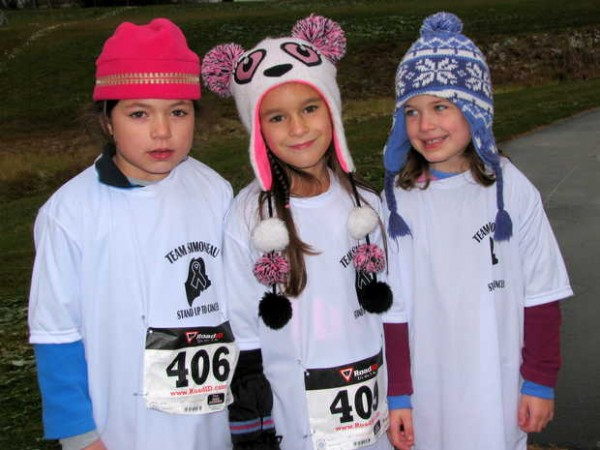 Taking a break from warming up for Saturday afternoon's Running for Randy 1-mile family fun run/walk event at Spruce Mountain High School are 7-year-old Clorinda Simoneau, left, Madison Simoneau, 7, and Sarah Simoneau, 5. Clorinda and Sarah live in Durham, and Madison lives in Chester, N.H. The girls were wearing Stand Up To Cancer jerseys for Team Simoneau.