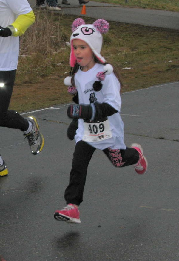 Madison Simoneau, 7, of Chester, N.H., runs in Saturday's 1-mile family fun run/walk event, the first of two events in Running for Randy, a Spruce Mountain High School fundraiser in Jay for beloved running, race-walking and skiing coach and educator Randy Easter, who is battling cancer.