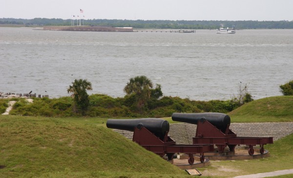 Two cannons peer over the parapet at Fort Moultrie, located on Sullivan's Island near Charleston, S.C. In the distance flags wave above Fort Sumter. Confederate troops garrisoned both forts during the Civil War, and from Fort Moultrie Confederate gunners hammered the grounded ironclad USS Lehigh at dawn on Nov. 16, 1863.