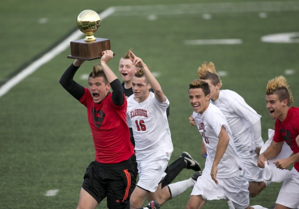 Scarborough goalie Patrick Stanton races across the field with the Gold Ball after his team defeated Hampden Academy in the Class A boys soccer state championship, Saturday, Nov. 9, 2013, in Bath.