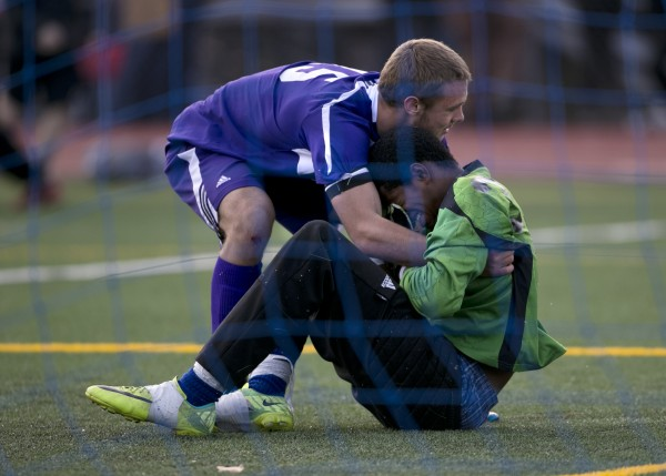 Hampden Academy goalie Isaiah Best (right) is consoled by teammate Cameron Scott after giving up a goal in the overtime loss to Scarborough in the Class A boys soccer state championship, Saturday, Nov. 9, 2013, in Bath.