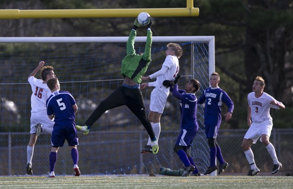 Hampden Academy goalie Isaiah Best leaps to makes a save in the second half against  Scarborough in the Class A boys soccer state championship, Saturday, Nov. 9, 2013, in Bath.