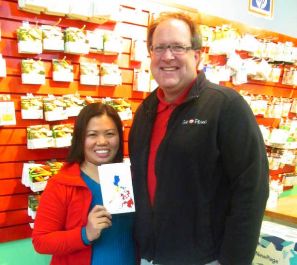 Cherry Smith of Mexico holds a map of the Philippines on Wednesday with her husband, Randall, inside their Rumford store, Ink Plaza. Cherry Smith was born on the island of Negros in the Philippines and lived there until 2008.