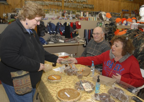 Approximately seven months out of each year, the Simpson Memorial Library trustees hold a bake sale at Ye Olde General Store on Route 2 in Carmel to raise funds for the nonprofit library. Among the trustees staffing the table during the Nov. 16 bake sale were Eric Goodale (center) of Carmel and Linda Ricker (right), also of Carmel, who is the vice president of the board of trustees.