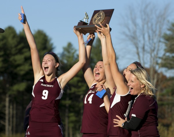 Foxcroft Academy captains Amber Anderson (from left), MacKenzie Coiley, and Emily Higgins, along with coach Stephanie Smith, celebrate with the trophy after defeating North Yarmouth Academy in the Class C field hockey state championship game Saturday, Nov. 2, 2013, in Yarmouth, Maine.
