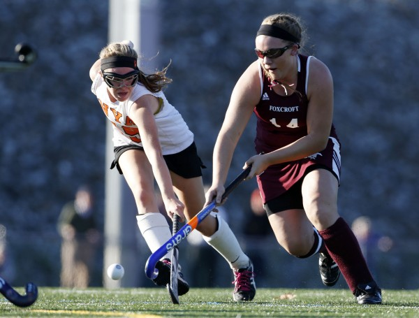 Foxcroft Academy's MacKenzie Coiley beats out North Yarmouth Academy's Marina Poole in a chase for the ball in the Class C field hockey state championship game Saturday, Nov. 2, 2013, in Yarmouth, Maine.