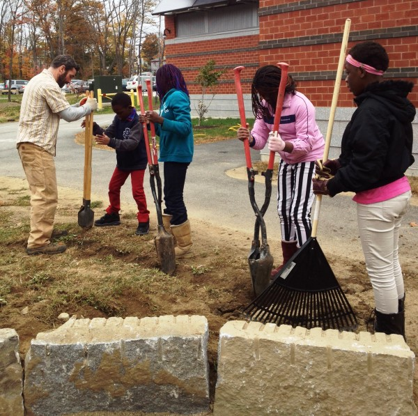 Jaime Parker of Portland Trails works with fourth graders to dig the garden.