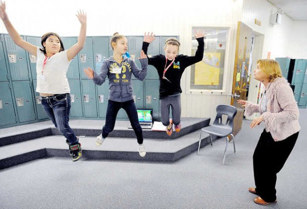 Students from the Maine French Heritage Language Program find a creative way to learn the French song, &quotBateau Sur L'eau,&quot (&quotBoat on the Water&quot) at Sherwood Heights Elementary School in Auburn. French teacher Diane Pelletier-Perron works with fifth-graders, from left, Hailey Strout, Morgan Giard and Lily Vincent.