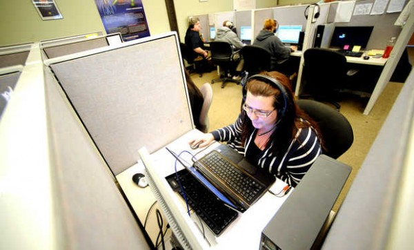 Heidi Gatchell of Auburn answers a call in Argo Market Group's call center on the second floor of the Key Bank Building on Lisbon Street recently.