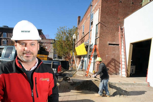 Argo Marketing Group CEO Jason Levesque stands in the courtyard of Dufresne Plaza between Lisbon and Park Streets in Lewiston as a construction crew works on the interior and exterior of his company's future call center.