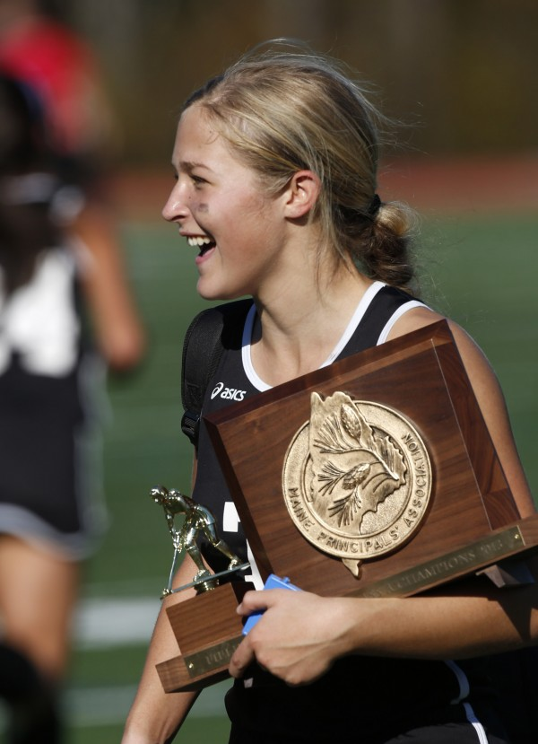 Skowhegan's Mikayla Toth carries the trophy after leading her team to the Class A field hockey state championship game over Scarborough on Saturday, Nov. 2, 2013, in Yarmouth, Maine.