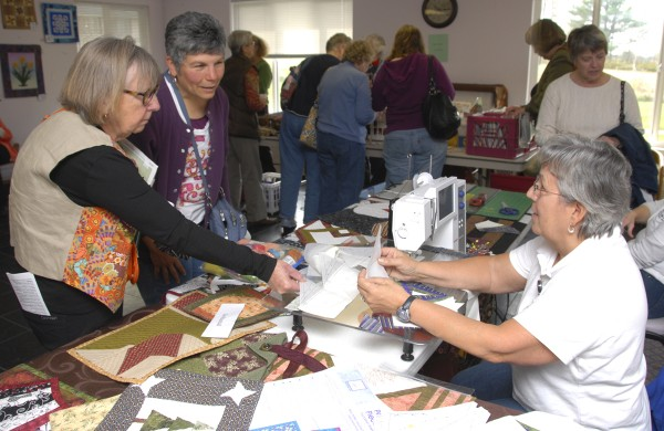 While attending the Bangor Bear Paw Qult Show held at Sunbury Village on Ohio Street, (from left) Elizabeth Hall of Bar Harbor and Pier Carros of Ellsworth discuss a demonstration of strip-paper piecing with Sue Randall of Canoe City Quilters.