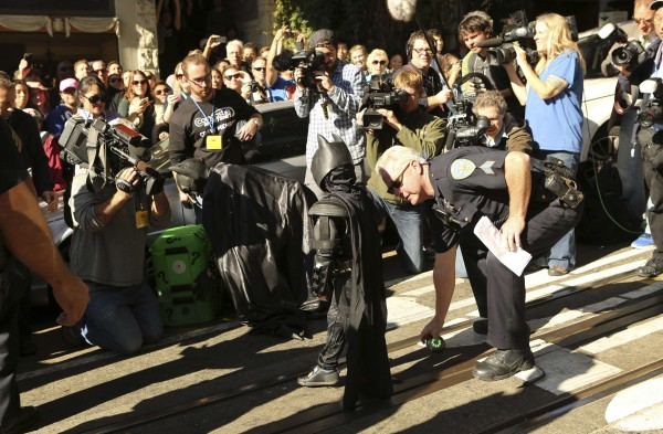 Five-year-old leukemia survivor Miles dressed as &quotBatkid&quot is assisted by a police officer as he works with a man dressed as Batman (left) to defuse a device as part of a day arranged by the Make-A-Wish Foundation in San Francisco, Calif., Nov. 15, 2013.