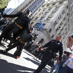 "Five-year-old leukemia survivor Miles dressed as ""Batkid"" and a man dressed as Batman are escorted by police officers back to their Batmobile after they apprehended the ""Riddler"" as part of a day arranged by the Make-A-Wish Foundation in San Francisco, Calif., Nov. 15, 2013."