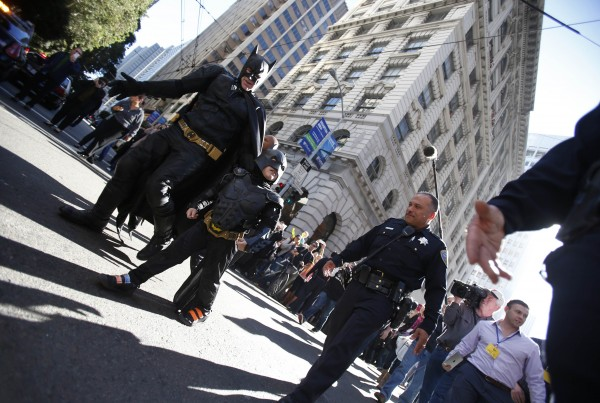 Five-year-old leukemia survivor Miles dressed as &quotBatkid&quot and a man dressed as Batman are escorted by police officers back to their Batmobile after they apprehended the &quotRiddler&quot as part of a day arranged by the Make-A-Wish Foundation in San Francisco, Calif., Nov. 15, 2013.