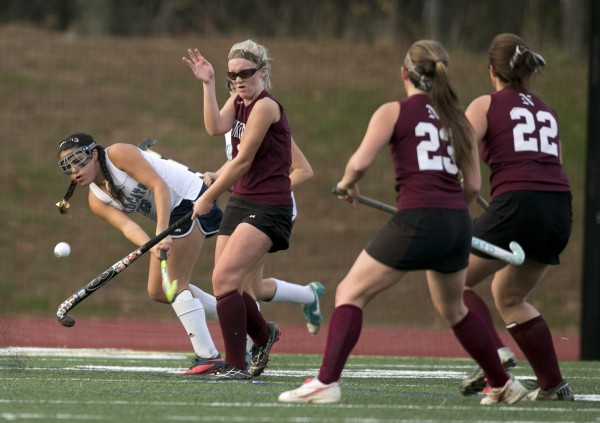 Nokomis' Lyndsay Whitney turns away from a shot by York's Kiyanna Hutchins in the first half of the Class B field hockey state championship game Saturday, Nov. 2, 2013, in Yarmouth, Maine.