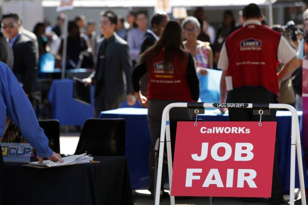 Job fair attendees browse displays at Los Angeles City College in October. Given the economic climate, more companies are investing in software instead of adding to their payrolls.