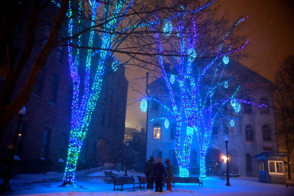 Three people stand in Tommy's Park in Portland's Old Port in the wee hours of Sunday morning amid the falling snow and holiday light show.