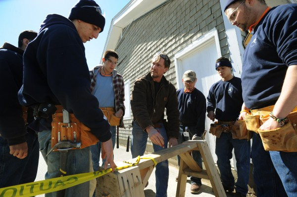Mark Martin, center, instructor at the Home Builders Institute on the Penobscot Job Corp campus draws a sketch on a saw horse to show his students the next step in laying out a building in the parking lot of the center on Thursday, April 7, 2011.