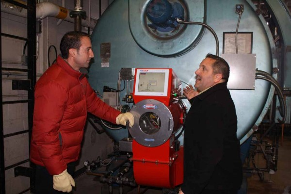 Jim Cavagnaro (right) Cary Medical Center manager of facilities, explains the operation of the hospital's newly converted boilers to Doug Plourde of the Caribou Hospital District Board. On Dec. 20, Cary marked its official changeover to compressed natural gas as its major fuel source. Part of the process was the conversion of its four primary boilers for use with both gas and fuel oil.