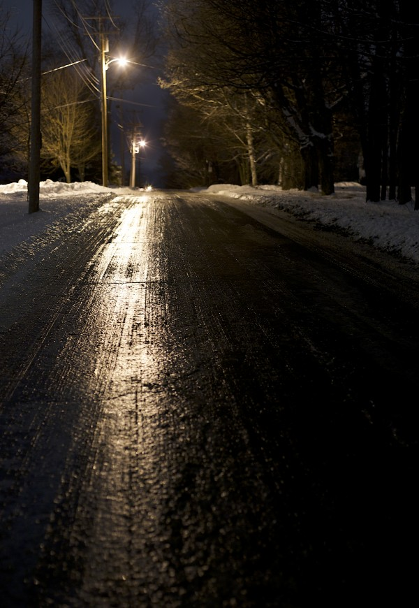 Street lights reflect off ice-covered Webster Avenue, which bisects the Bangor Municipal Golf Course, on Saturday evening during a storm. Meteorologists predicted up to three-quarters of an inch of ice accumulation late Saturday into Sunday.